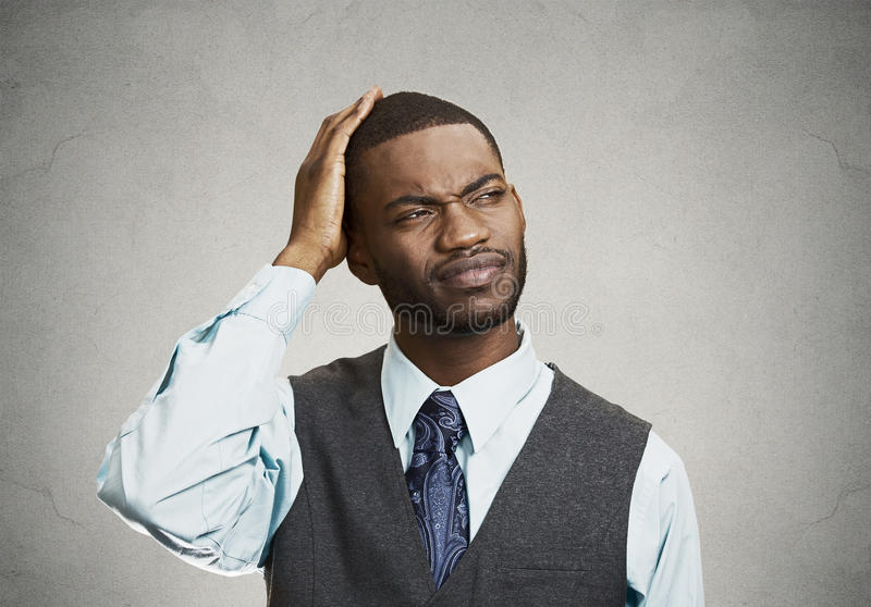 Confused man looks up on gray background stock photography