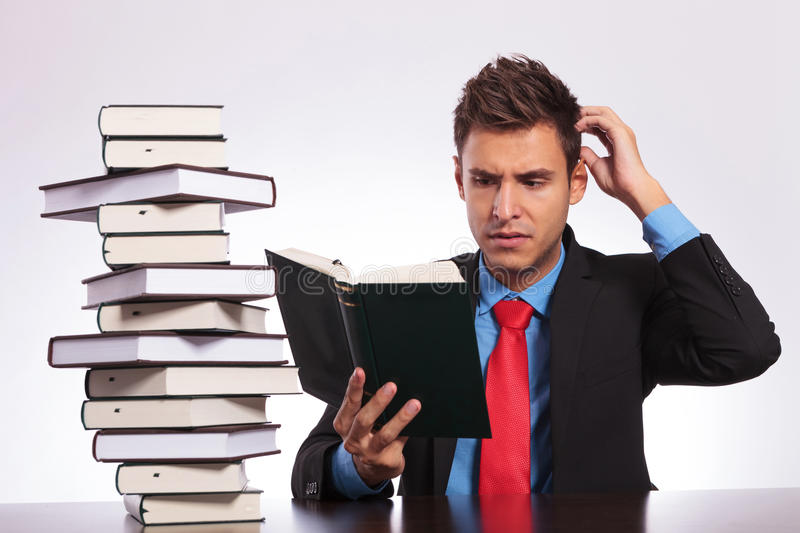 Confused man reading at desk royalty free stock photo