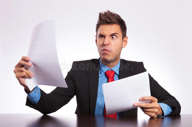 Confused man reading at desk stock photo