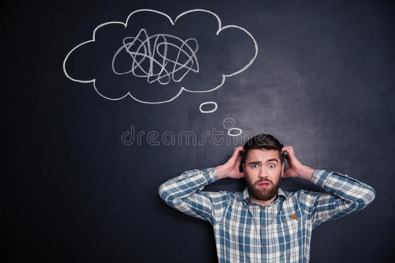 Confused man thinking about problem with black board behind him royalty free stock image