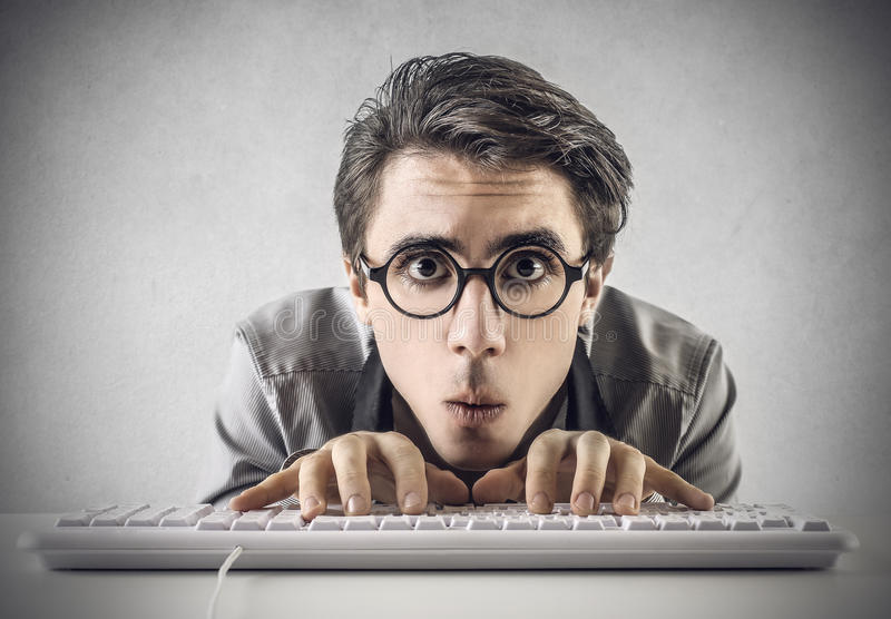 Confused man typing on the keyboard stock images
