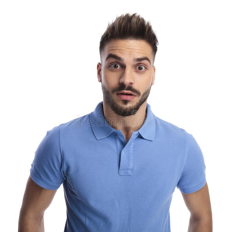 Confused man wearing a light blue polo being surprised. While looking at the camera on alight background stock image