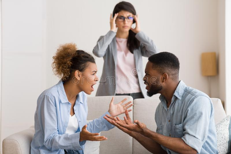 Confused Marital Psychologist Witnessing Afro Couple Arguing In Office. Marriage Therapy. Shocked Marital Psychologist Witnessing Afro Patients Arguing royalty free stock images