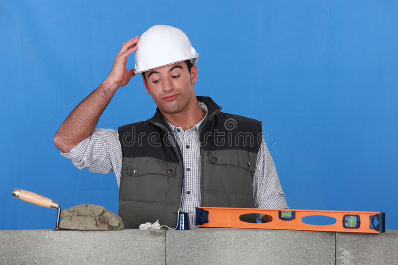 Confused mason. Stood by unfinished wall royalty free stock photos