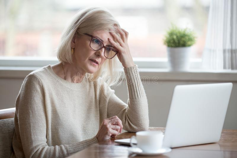 Confused mature woman thinking about online problem looking at l. Thoughtful confused mature business woman concerned thinking about online problem looking at royalty free stock image