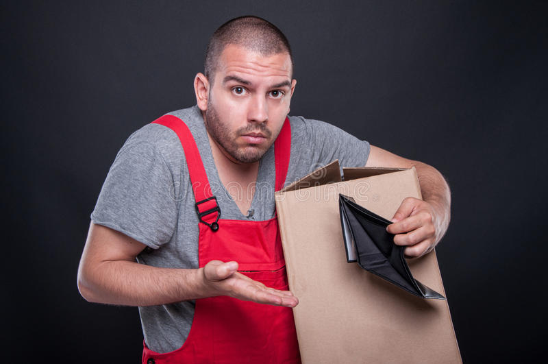 Confused mover man holding box showing empty wallet royalty free stock photo