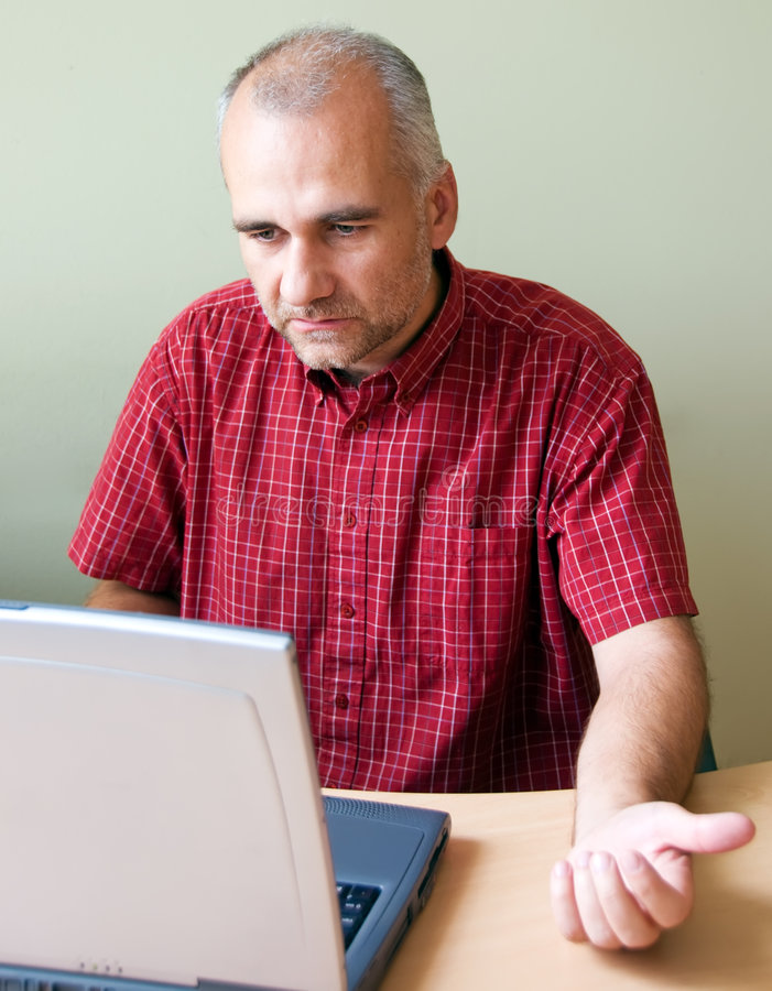 Confused office worker. Working at the desk with laptop royalty free stock photography