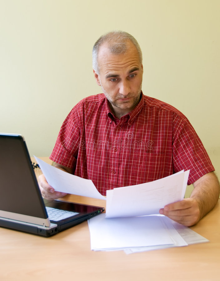 Confused office worker. Studying sale report at the desk with laptop stock images