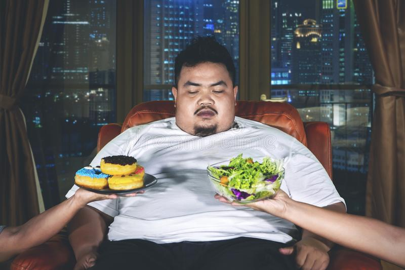 Confused overweight man chooses food stock photography