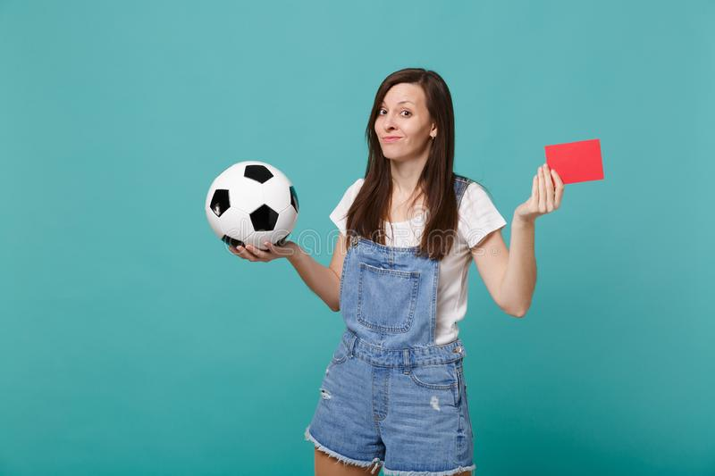 Confused puzzled young woman football fan support team with soccer ball, red card propose player retire from field. Isolated on blue turquoise background royalty free stock photography