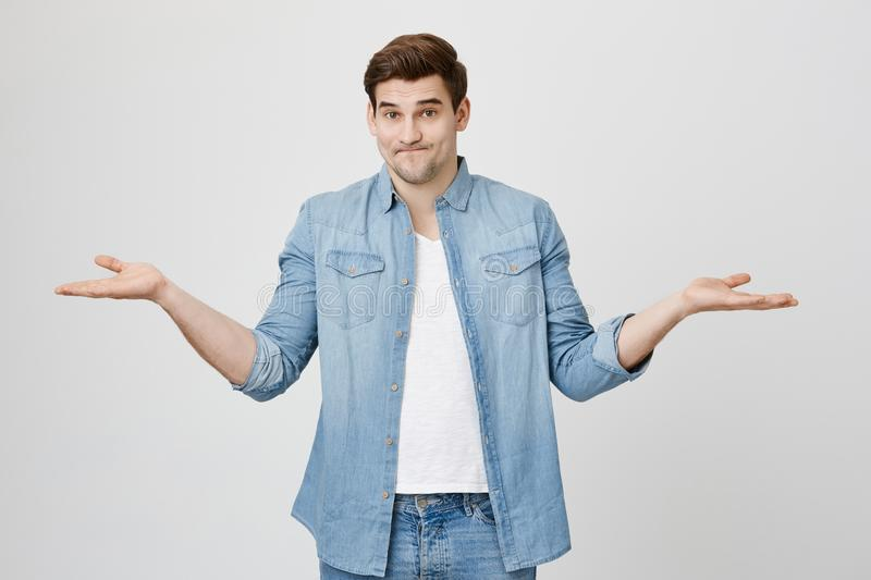 Confused and questioned young guy with stylish haircut, shrugging shoulders while stretching hands in uncertainty. Gesture, over gray background. Guy do not royalty free stock photo