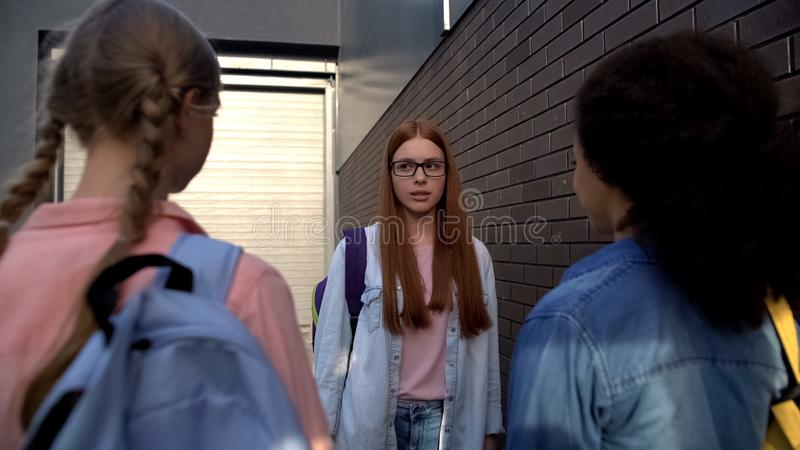 Confused red-haired teenager in eyeglasses standing front of cruel classmates. Stock photo royalty free stock images
