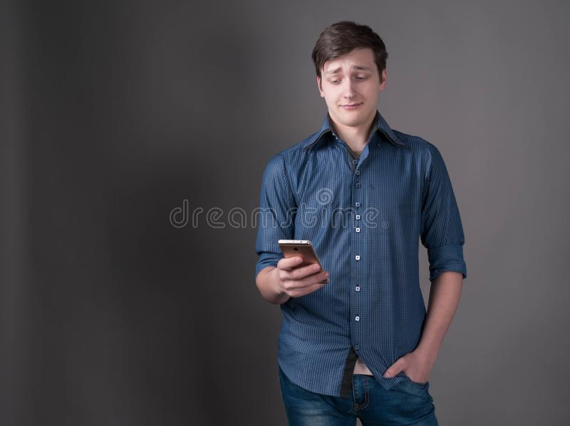 Confused and scared young man with dark hair in blue shirt, holding hand in pocket and looking at smartphone. In front of gray background royalty free stock photo