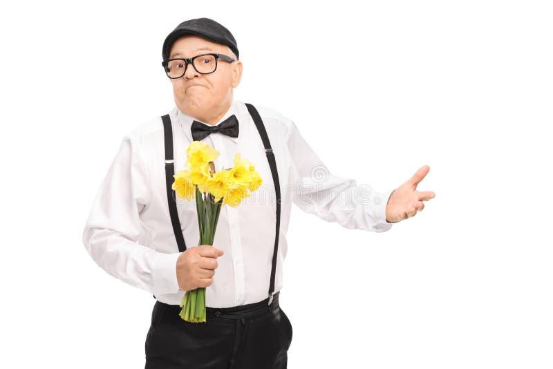 Confused senior gentleman holding flowers royalty free stock photos