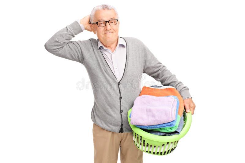 Confused senior holding a laundry basket royalty free stock image