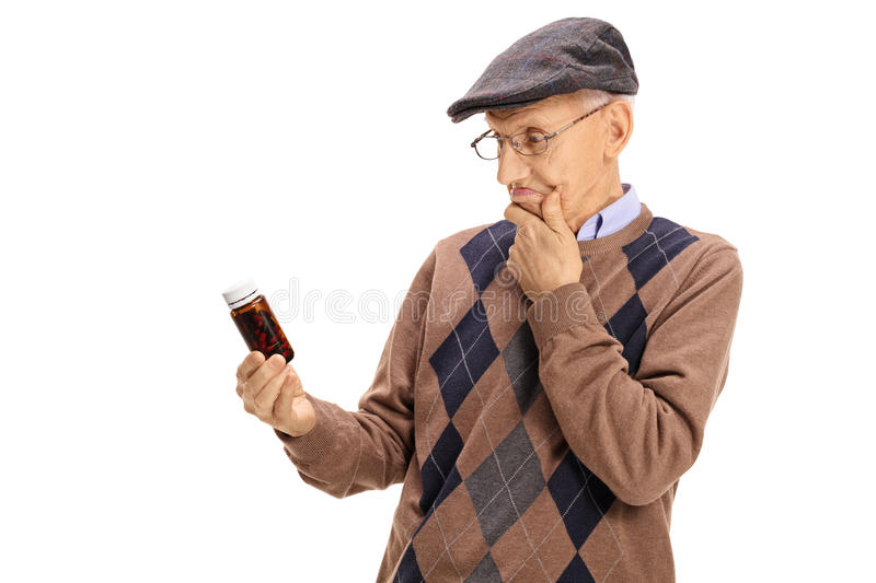 Confused senior looking at a bottle of pills stock image
