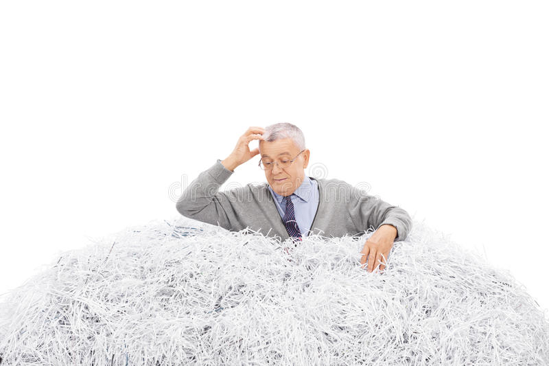 Confused Senior Looking In Pile Of Shredded Paper Stock