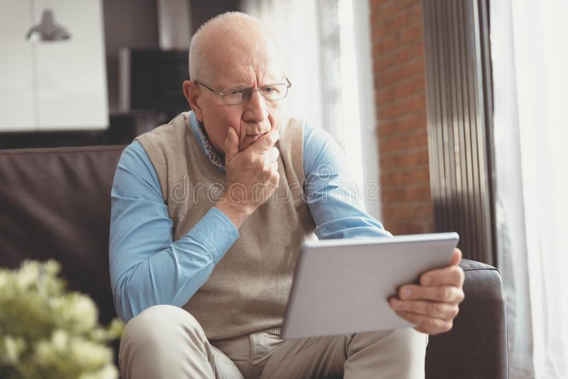 Confused senior man using a digital tablet royalty free stock image