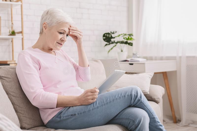 Confused senior woman using tablet computer at home. Confused senior woman using tablet computer, looking disappointed, doesn`t understand modern gadgets, empty stock image