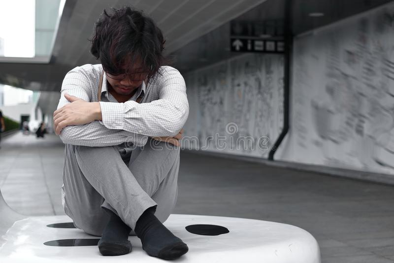 Confused sitter kramar den utmattade unga asiatiska affärsmannen och hans knä upp till bröstkorgen royaltyfri fotografi
