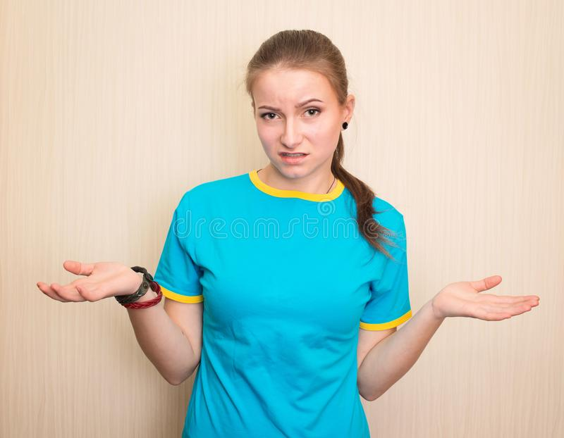 Confused teen girl shrugging shoulders and looking at camera aft. Er she did something wrong but not feeling sorry or guilty royalty free stock images