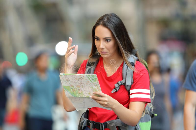 Confused teen tourist searching location. In a paper guide walking on the street stock image