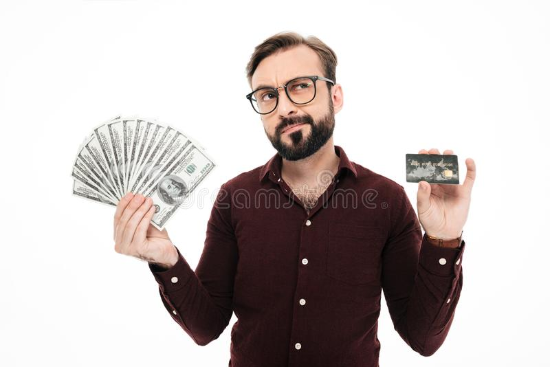 Confused thinking young man holding money and credit card. stock image