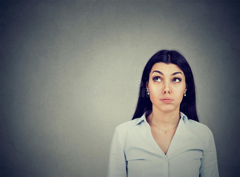 Confused thoughtful young woman making up her mind royalty free stock photo