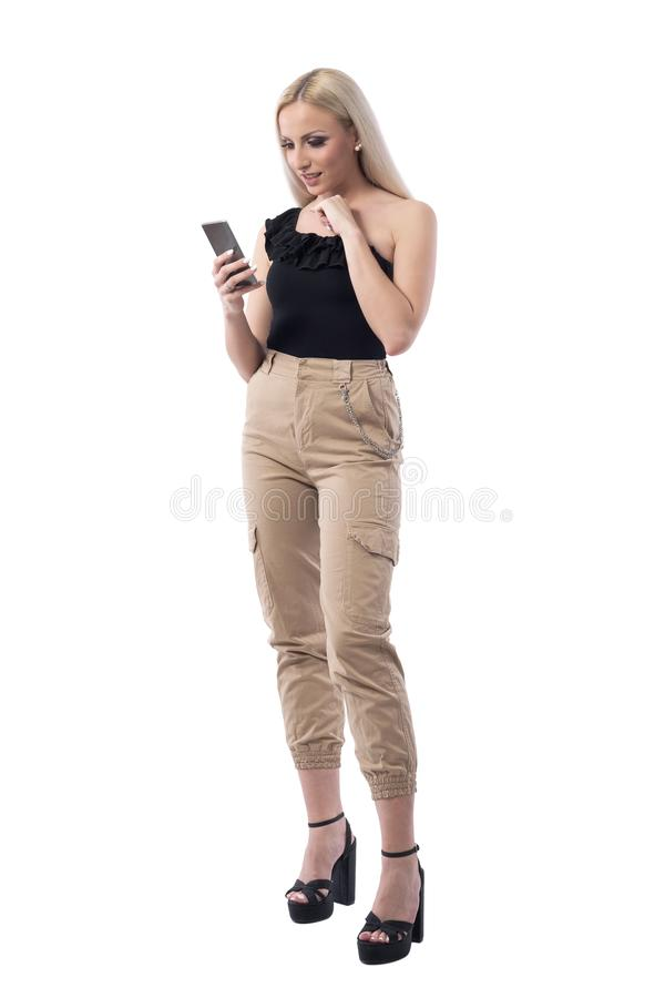 Confused uncertain young blonde woman reading and using smart phone social media. stock images