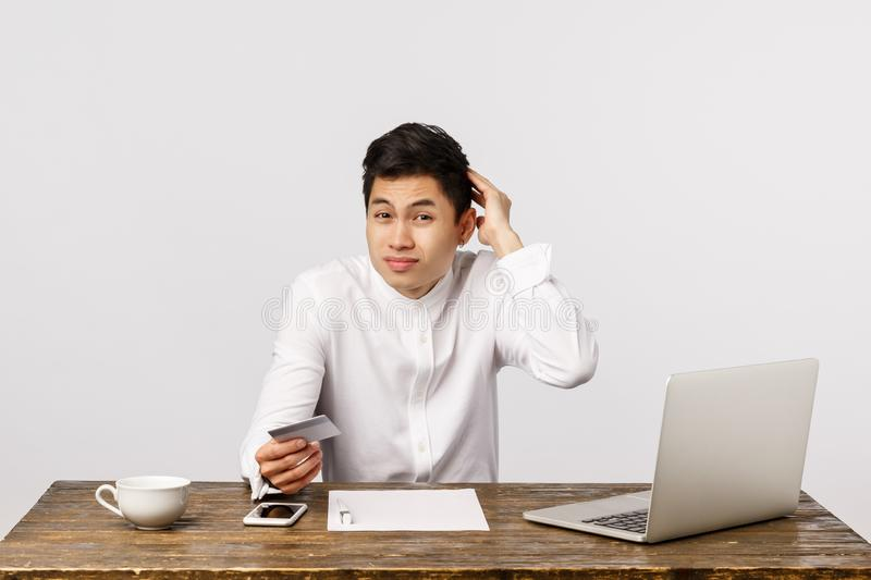 Confused, unsure young asian guy, office worker, sitting table near laptop, documents, scratching head hesitant stock images