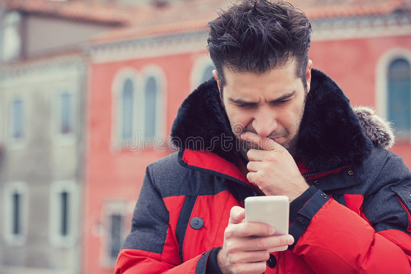 Confused upset man looking at his mobile phone standing outdoors stock images