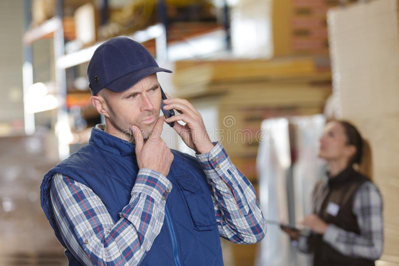 Confused warehouse woeker on phone stock photography