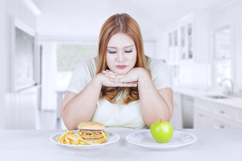 Confused woman choose apple or hamburger. Picture of blonde woman looks confused to choose a fresh apple fruit or hamburger, shot in the kitchen stock image