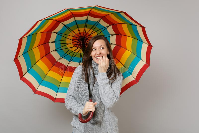 Confused woman in gray sweater, scarf looking up, gnawing nails, hold colorful umbrella isolated on grey background. Healthy fashion lifestyle people emotions stock images