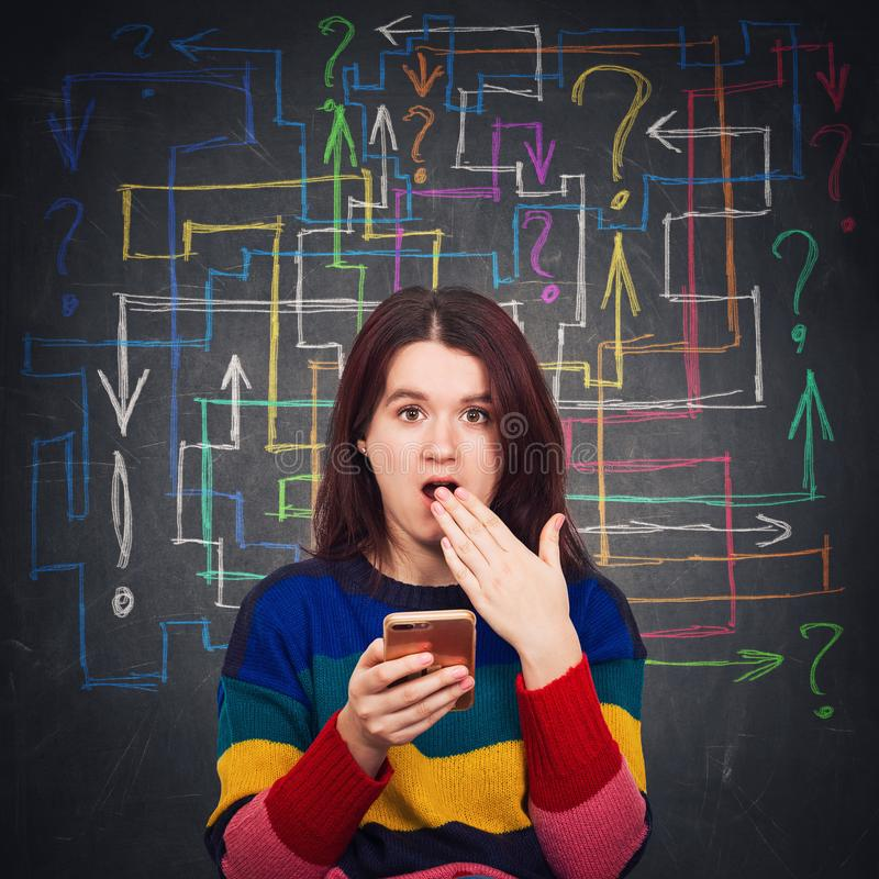 Confused woman. Confused young woman using her phone shocked open mouth emotion. Human reaction concept as different colorful arrows and questions marks makes a royalty free stock photos