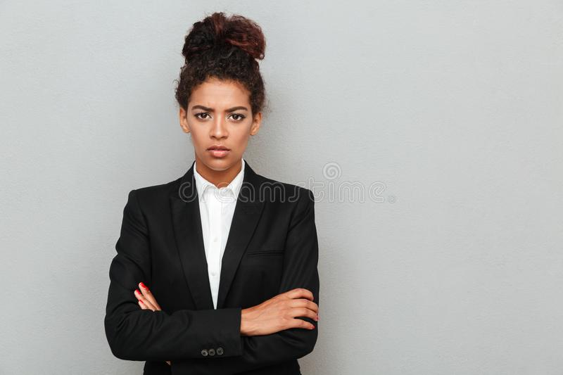 Confused young african business woman standing over grey wall. Picture of confused young african business woman standing over grey wall looking camera royalty free stock image