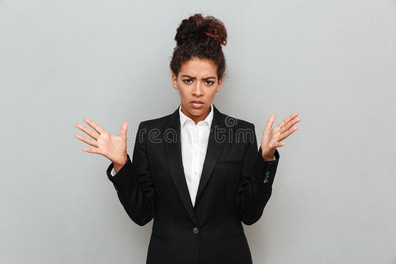 Confused young african business woman standing over grey wall. Picture of confused young african business woman standing over grey wall looking camera stock photos