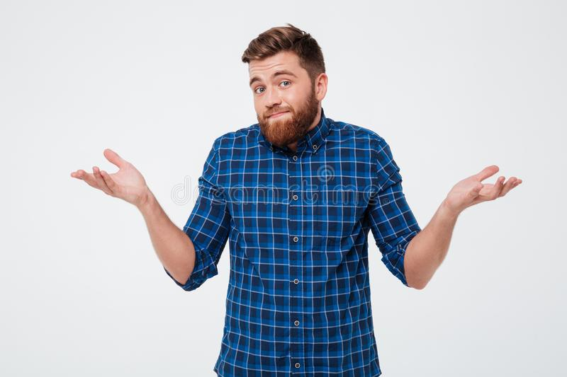 Confused young bearded man standing. And shrugging shoulders over white background stock photography