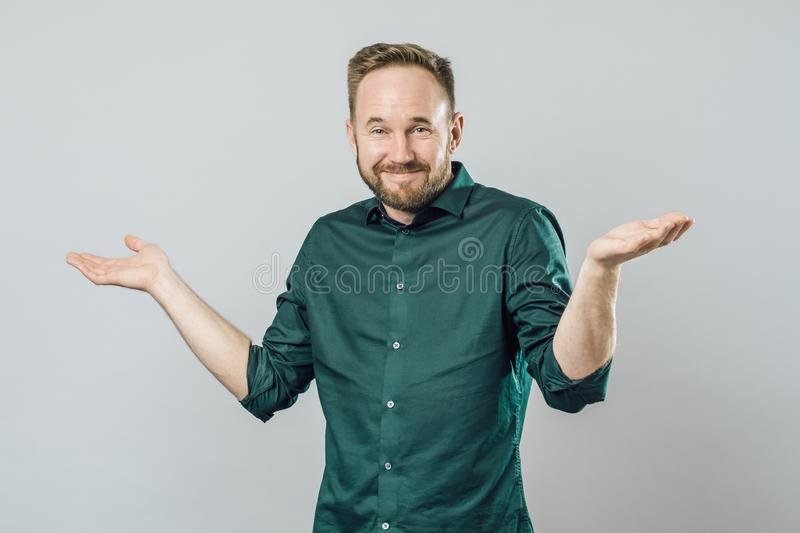 Confused young bearded man standing and shrugging shoulders. Gray white background royalty free stock photography