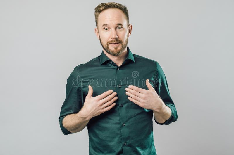 Confused young bearded man standing and shrugging shoulders. Isolated gray white background stock photos