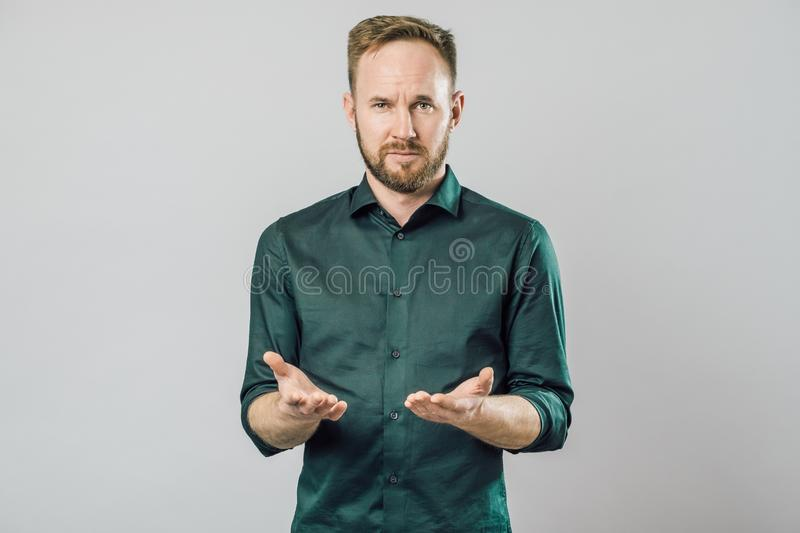 Confused young bearded man standing and shrugging shoulders. Isolated gray white background royalty free stock photography