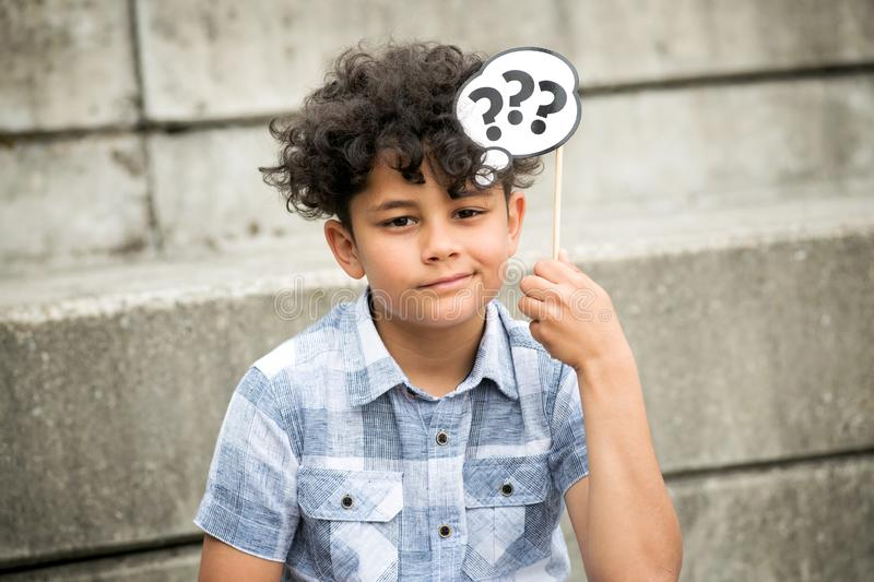 Confused young boy with question marks stock photo