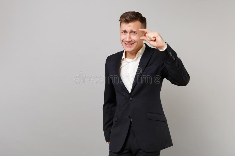 Confused young business man in classic black suit, shirt gesturing demonstrating size with copy space isolated on grey. Wall background. Achievement career royalty free stock image
