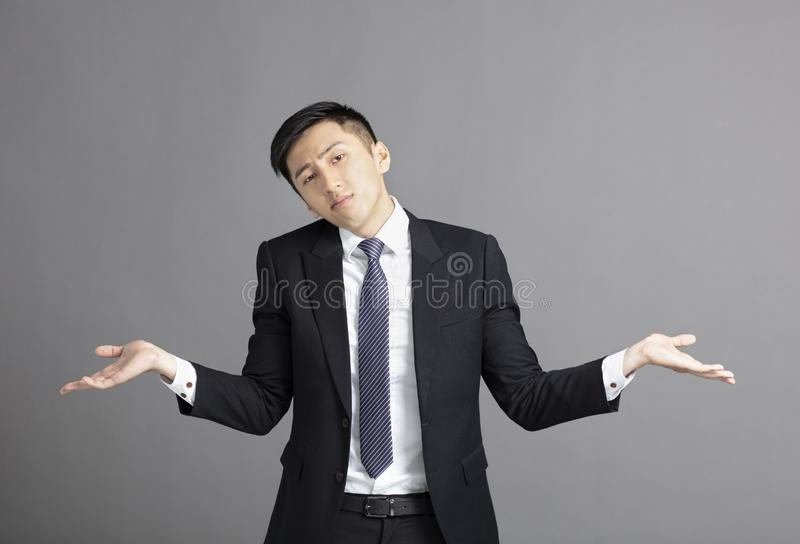 Confused young businessman shrugging shoulders. Confused young asian businessman shrugging shoulders stock photos