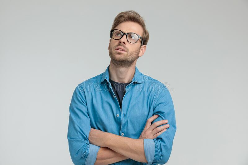 Confused young casual man looking up and thinking royalty free stock photos