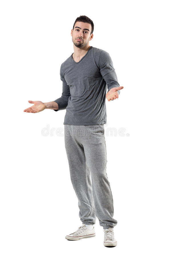 Confused young fit sporty man shrugging shoulders looking at camera royalty free stock images