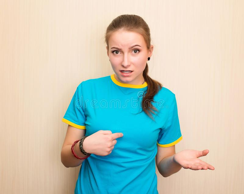 Confused young girl shrugging shoulders and looking at camera after she did something wrong but not feeling sorry or guilty. Who, me? Not me royalty free stock photography