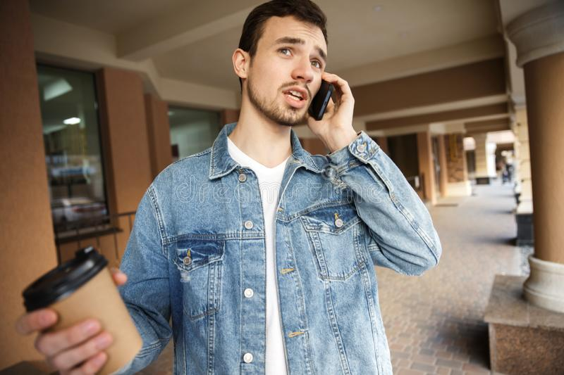 Confused young guy is talking on the phone while holding a paper cup in his right hand. He is standing on the street royalty free stock images