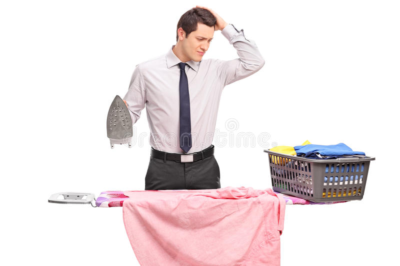 Confused young guy trying to iron his clothes. Studio shot of a confused young guy trying to iron his clothes isolated on white background stock photos