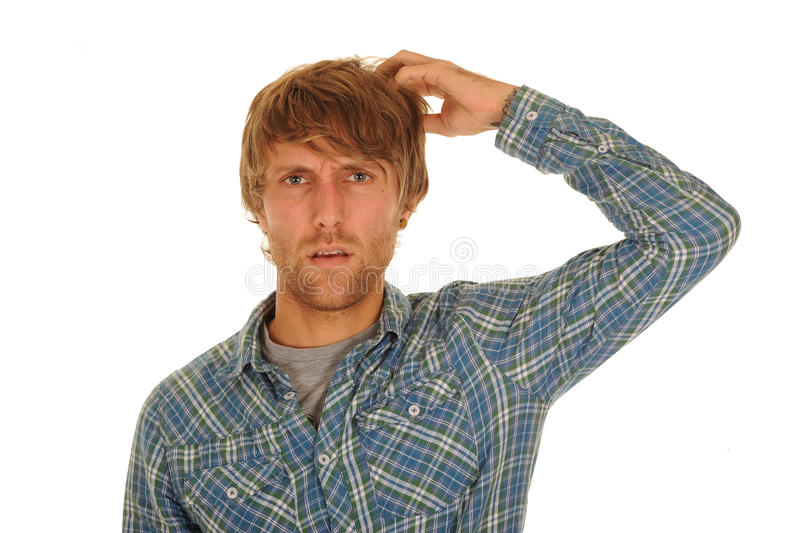 Confused young man. Portrait of confused young man in check shirt scratching head; isolated on white background royalty free stock photo